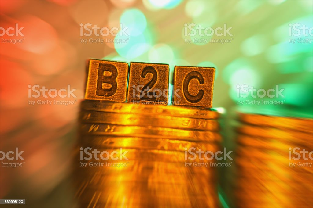 B2C copper alphabet on coin stack in radial blur illuminated with light stock photo
