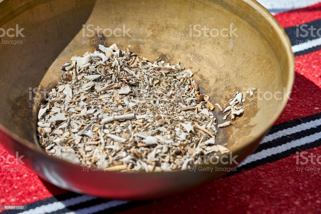 copper bowl of smudge stick sage leaves used for burning incense to clean and purify stock photo