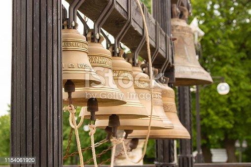 Copper brass metal church bells near the temple. Instrument ringer Orthodox Christian monastery. Bells engraved from scripture Christian Utensils