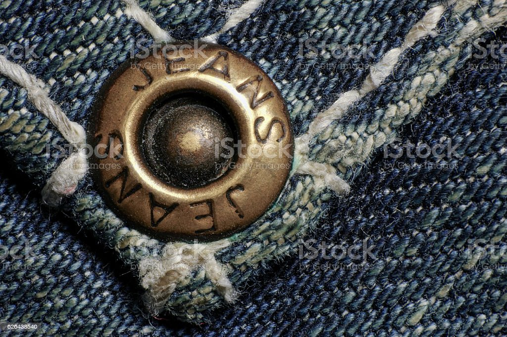 Copper button or rivet, old dirty jeans, macro foto. stock photo