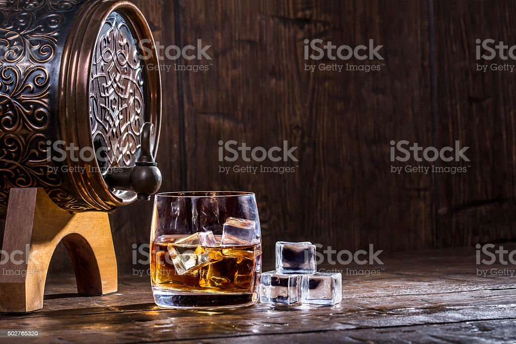 Copper forged barrel and a glass of whiskey and ice stock photo