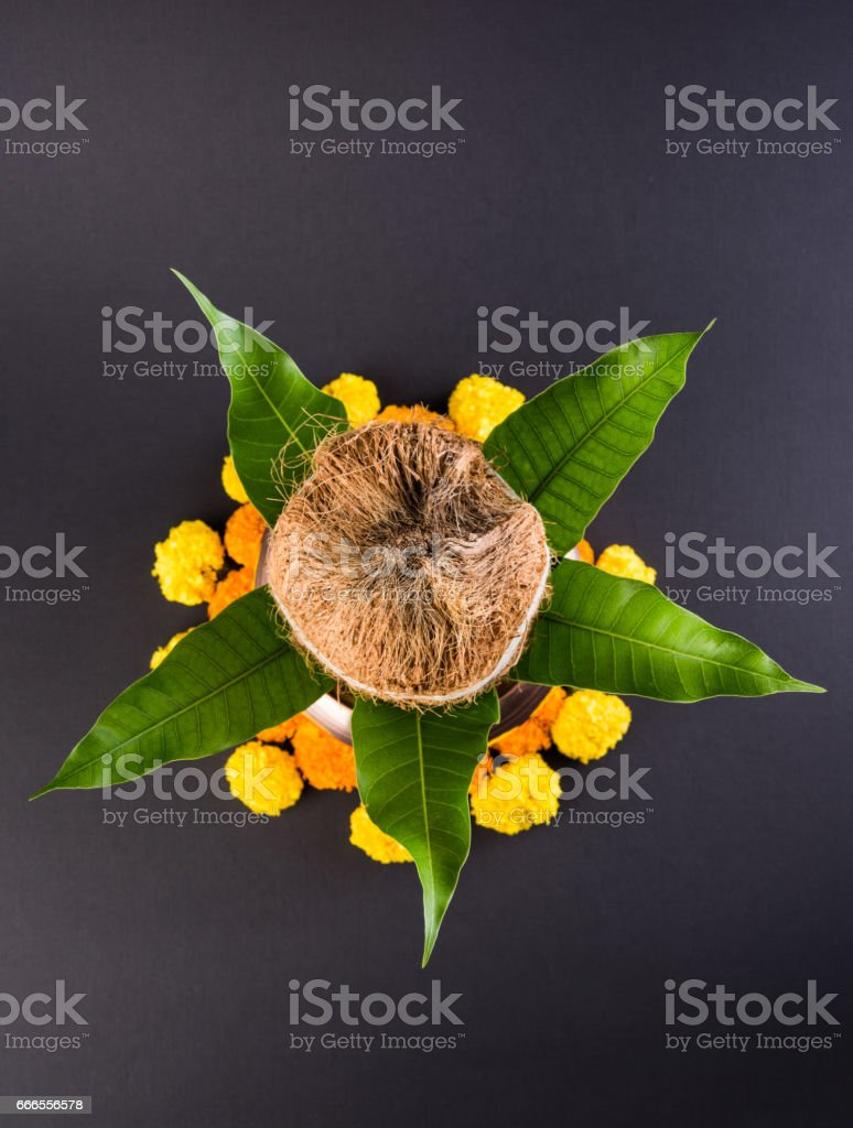 copper kalash with coconut and mango leaf with floral decoration. essential in hindu puja, selective focus, over plain background stock photo