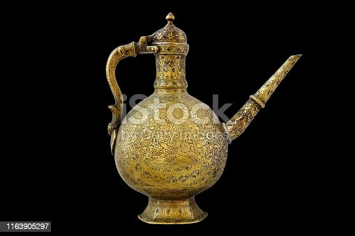 686515422istockphoto Copper kettle with patterns, kettle on black background. 1163905297