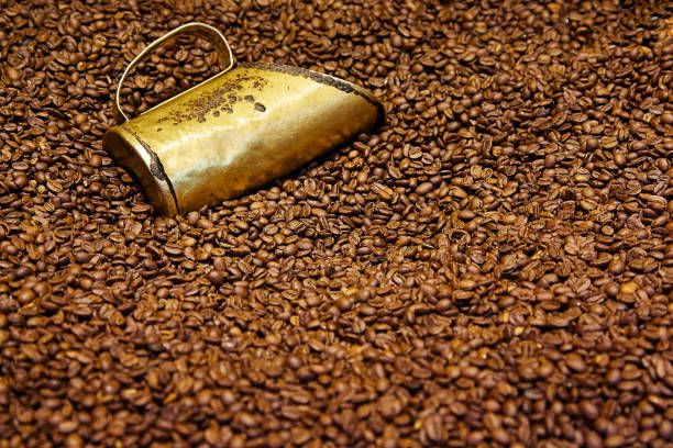 Copper measuring cup in coffee beans - foto stock