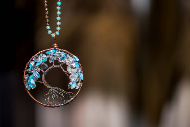Copper Pendant necklace with Aquamarine Stones. Tree of life on dark background Copper Pendant necklace with Aquamarine Stones. Tree of life on dark background amulet stock pictures, royalty-free photos & images
