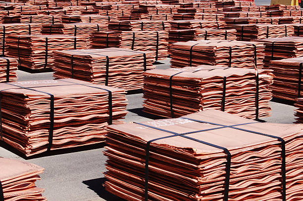 Copper Sheets Sheets, or cathodes, of 99.99% pure copper sit in stacks outside a solvent-extraction plant awaiting shipment. Each stack is strapped with steel and arranged in neat piles which fill the image. Each stack is worth $15,000.  anode stock pictures, royalty-free photos & images