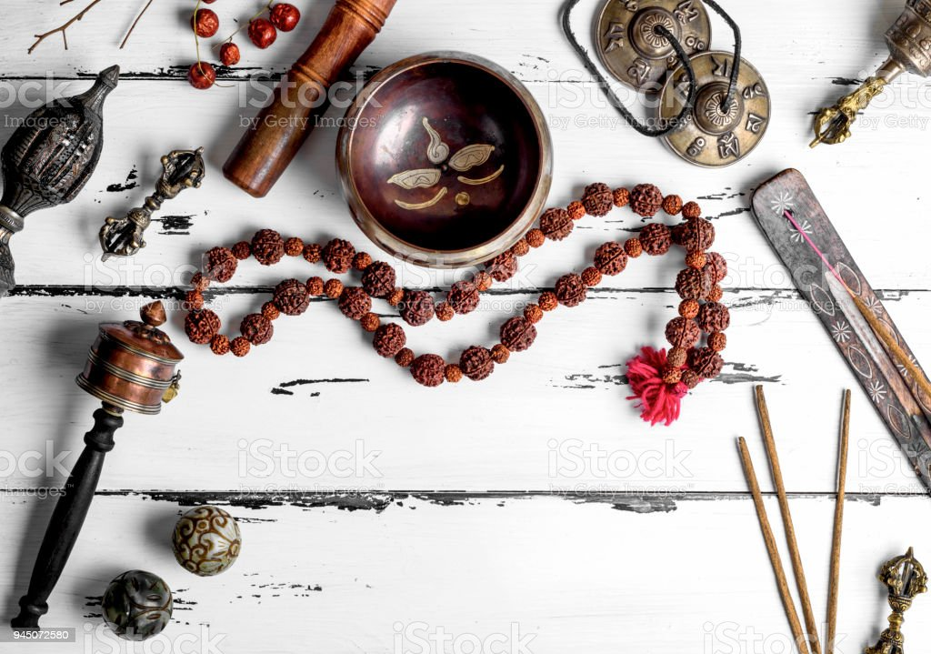 Copper singing bowl, prayer beads, prayer drum, stone balls and other Tibetan religious objects stock photo