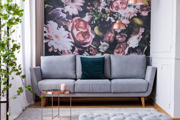 kupfer tisch auf teppich und grünen kissen auf graue couch im wohnzimmer interieur blumen. echtes foto - blumendrucktapete stock-fotos und bilder