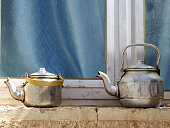 Copper teapots standing to concrete sill, kettles on street shop window before glass. Teapot consisting of copper kettles with handle, spout for draining liquid coffee. Copper kettles is iron teapots.