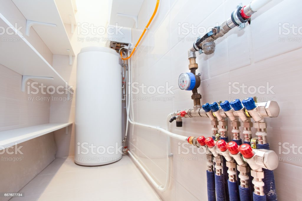 Copper valves, stainless ball valves and plastic pipes on a boiler room equipment in apartment during under renovation, remodeling and construction. stock photo