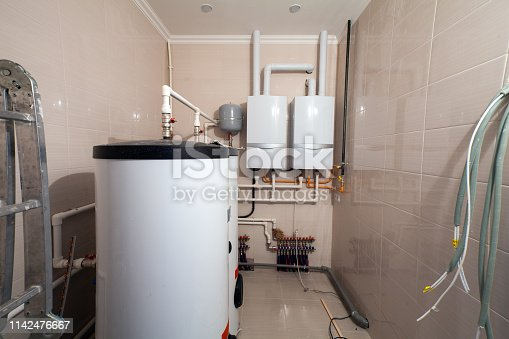 Copper valves, stainless ball valves,  detectors of water pressure and plastic pipes of central heating system and water pipes with thermal insulation in the  boiler room  in apartment during under renovation, remodeling and construction. Concept of independent private furnace room  or heat boiler station