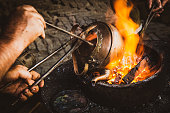 istock Coppersmith Repair Copper Kettle On Fire In Kashgar In Xinjiang 1298102169