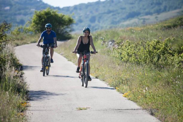 coppia di ragazzo e ragazza, gruppo di amici in bicicletta in montagna italiana - abruzzo cycle path foto e immagini stock