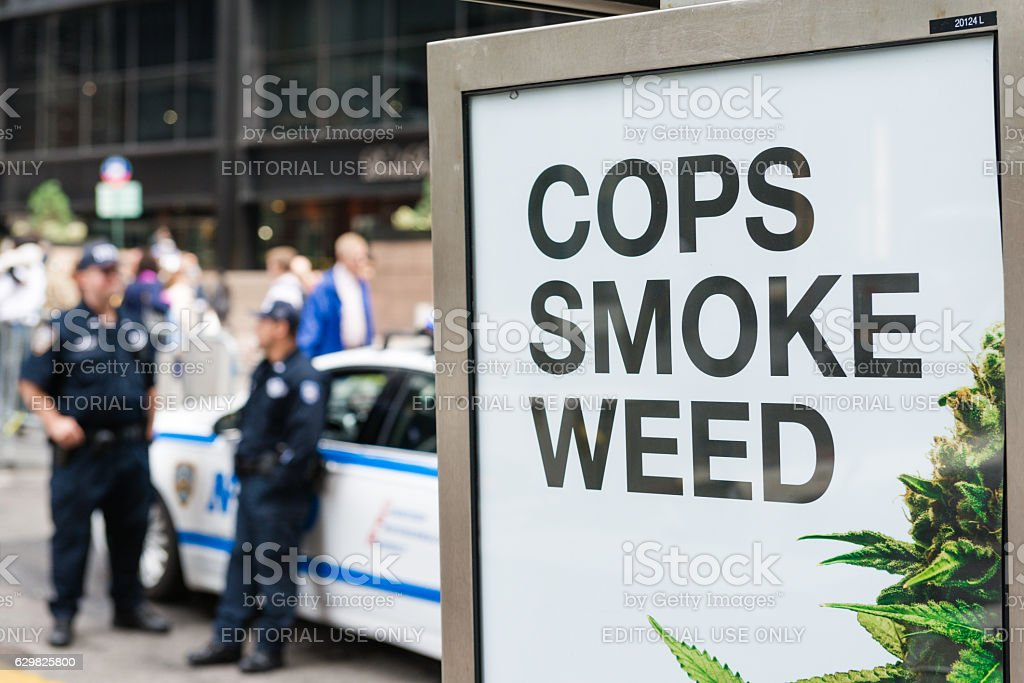 Cops Smoke Weed New York, USA - October 4, 2016: An advertisement that says Cops Smoke Weed on at phone booth on Church Street in lower Manhattan with two police officers standing next to a car late in the day. Addiction Stock Photo