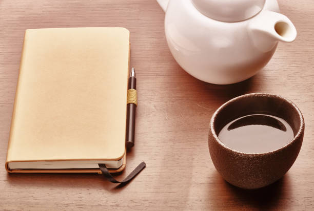 copy book, pen, teapot and cup of tea stock photo