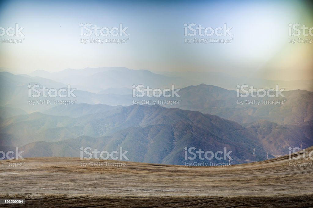 Copy space above real textured wood plank with beautiful mountain scene in background. Curved shape of wooden is stacked techniq. Use for product display. stock photo