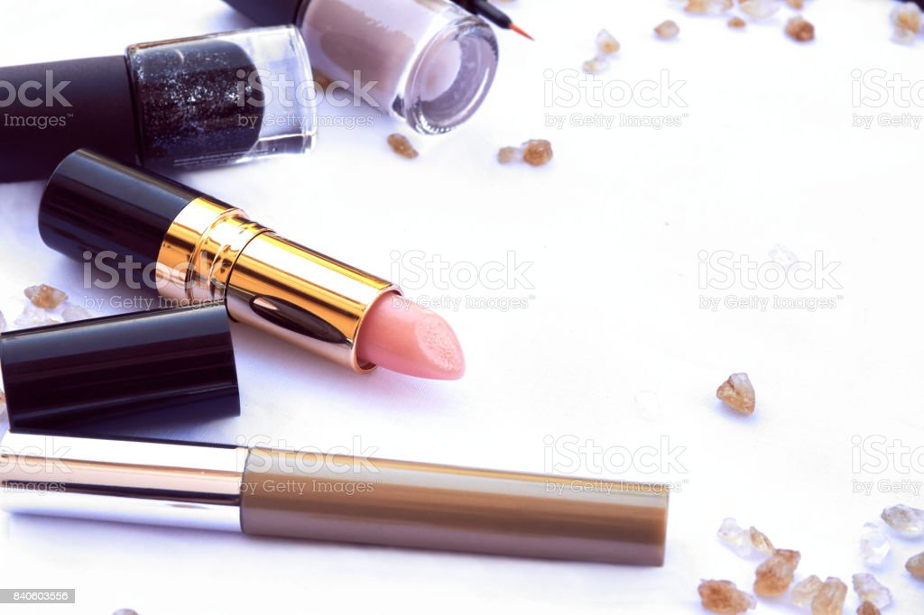 copy space flat lay top view cosmetic lipstick nail lacquer and brush purple brown tone  isolated on white stock photo