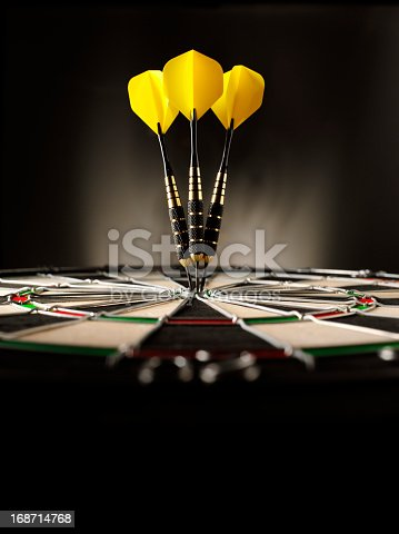 Three yellow darts hitting the target in a game of darts scoring a bulls eye. Copy space