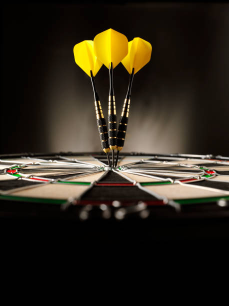 Copy Space in Darts Three yellow darts hitting the target in a game of darts scoring a bulls eye. Copy space dart stock pictures, royalty-free photos & images