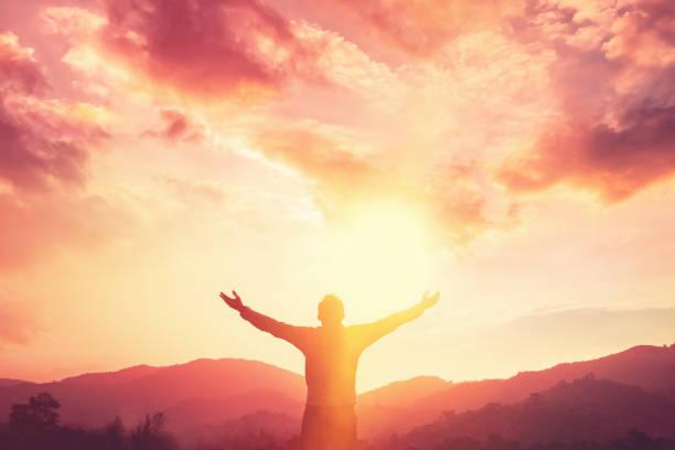 複製空間的人手舉在山頂和日落天空抽象背景。自由旅行冒險和商業勝利的概念。復古色調濾鏡效果顏色樣式。 - prayer 個照片及圖片檔