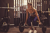 Full length shot of attractive young female athlete smiling while weightlifting heavy weights at the gym as a part of her workout routine.