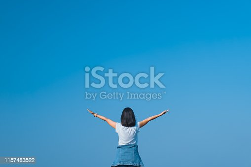 istock Copy space of woman raise hands up on empty blue sky abstract background. Freedom feel good and summer vacation holiday concept. Vintage tone filter effect color style. 1157483522