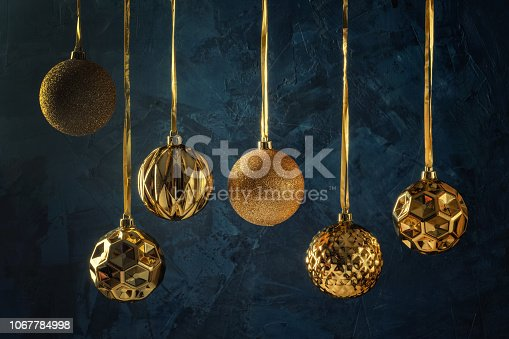 istock Copy space on a dark blue background with decorative putty textures. Six golden Christmas balls hanging on ribbons. Festive layout with place for text. 1067784998