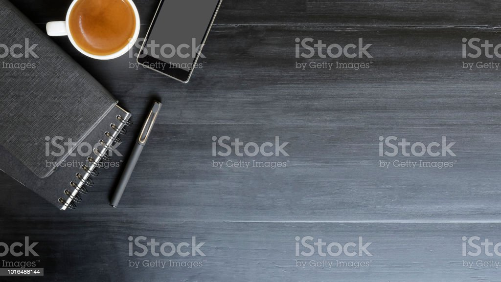 Copy space top view workspace with book and pen coffee cup on black...