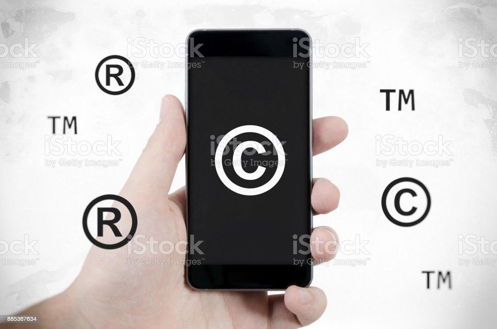 Copyright, trademark symbols flying around smartphone. stock photo
