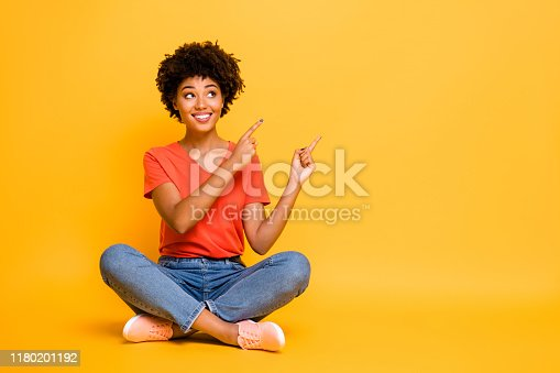 Copyspace photo of charming cheerful attractive gorgeous girlfriend sitting, with legs crossed wearing jeans denim footwear isolated with yellow bright color background