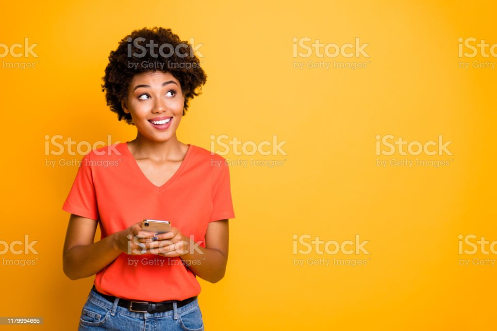 Copyspace photo of cheerful curly wavy trendy woman holding telephone with her hands wearing jeans denim orange t-shirt standing pensively looking up isolated over yellow vivid color background Copyspace photo of cheerful curly wavy trendy woman holding telephone with her hands wearing jeans denim orange t-shirt standing, pensively looking up isolated over yellow vivid color background Adult Stock Photo