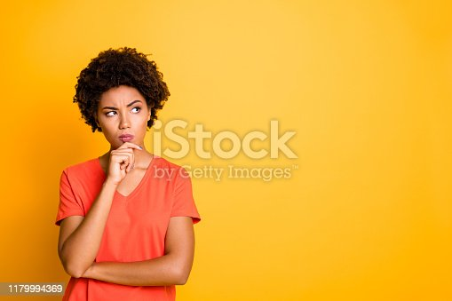 Copyspace photo of contemplating watching looking staring girlfriend wearing, orange t-shirt touching her chin pondering over something to choose isolated over yellow vivid color background