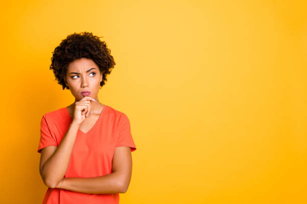 Copyspace photo of contemplating watching looking staring girlfriend wearing orange t-shirt touching her chin pondering over something to choose isolated over yellow vivid color background Copyspace photo of contemplating watching looking staring girlfriend wearing, orange t-shirt touching her chin pondering over something to choose isolated over yellow vivid color background skeptic stock pictures, royalty-free photos & images