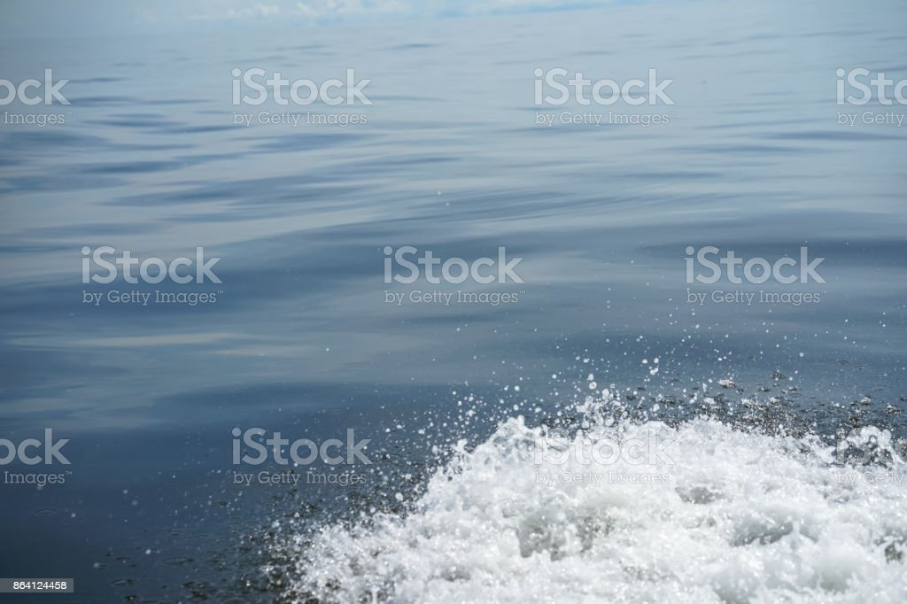Copyspace scene of gradient blue sea light ripple background with white bubble foam water splashing by running boat, freezing motion royalty-free stock photo
