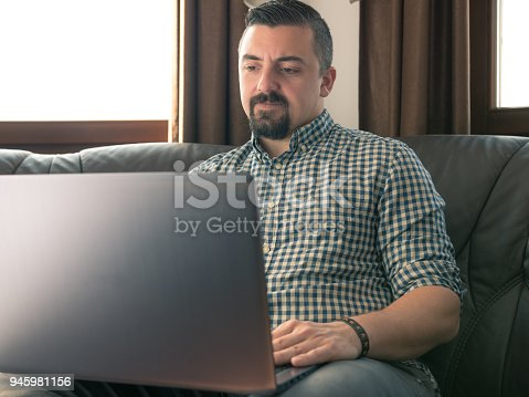 Copywriter working from home using his laptop. The man is casually dressed in shirt with rolled sleeves. The scene is situated indoors at a sofa in city apartment in Veliko Tarnovo, Bulgaria (Eastern Europe) during a sunny day. The photo was taken with Panasonic GH5 camera and Sigma Art 18-35mm lens.