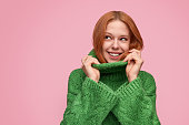 Charming female model with red hair and in green cozy sweater smiling away