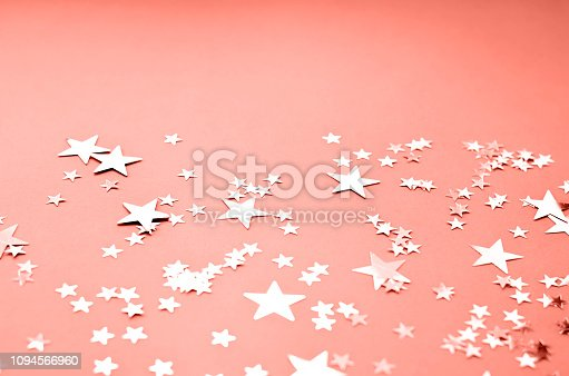 1040055260istockphoto A coral colored background with many shiny stars. 1094566960