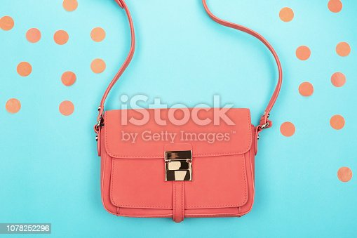 1078252566 istock photo Coral fashion bag on contrast background 1078252296