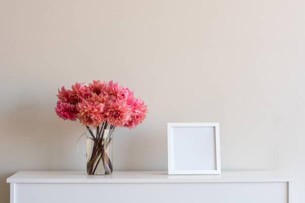 coral pink dahlien mit leeren quadratischen rahmen - anrichte weiß stock-fotos und bilder
