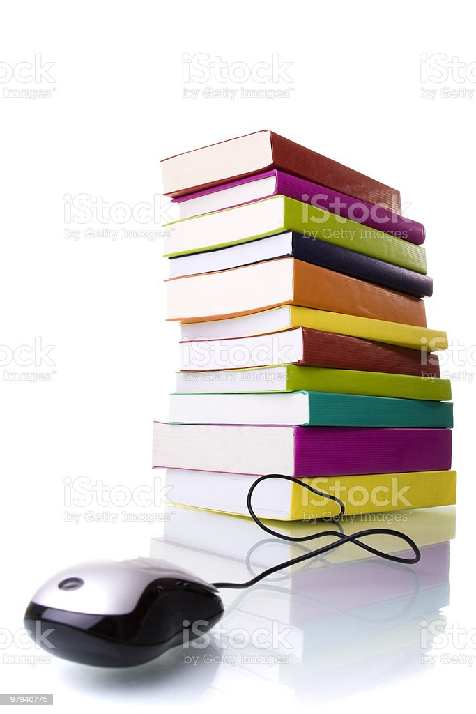 Corded mouse in front of tall stack of colorful books royalty-free stock photo