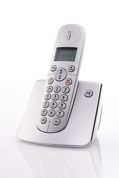 Cordless landline telephone on charger Cordless landline telephone in docking station cordless phone stock pictures, royalty-free photos & images