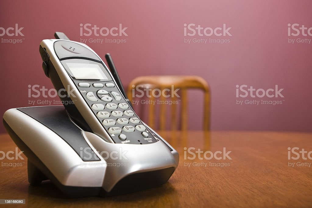 Cordless phone on a table with chair stock photo