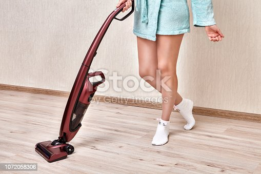 Cleaning lady in a blue robe cleans dust in the room with a cordless handheld vacuum.