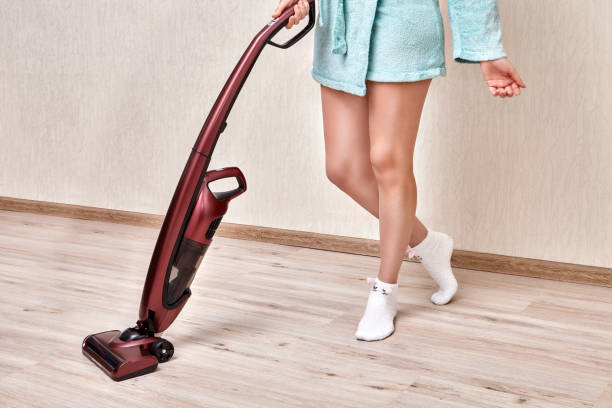 Cordless stick vacuum in hands of woman in home robe. Cleaning lady in a blue robe cleans dust in the room with a cordless handheld vacuum. cordless phone stock pictures, royalty-free photos & images