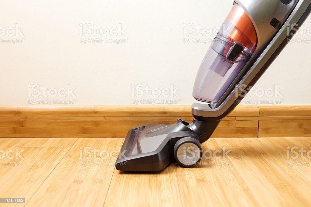 Linee verticali aspirapolvere pulizia pavimento in parquet. - foto stock