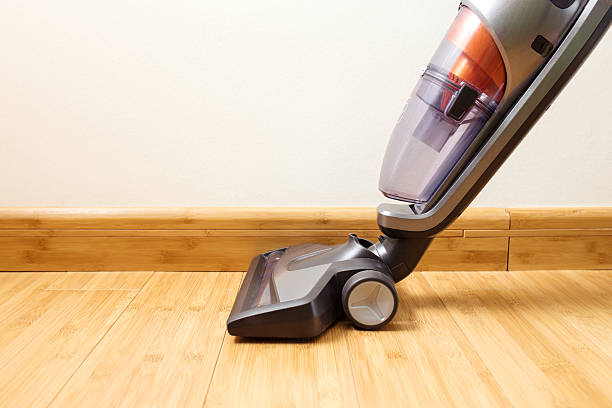 cordless vertical vacuum cleaner cleaning parquet floor. - stofzuiger stockfoto's en -beelden