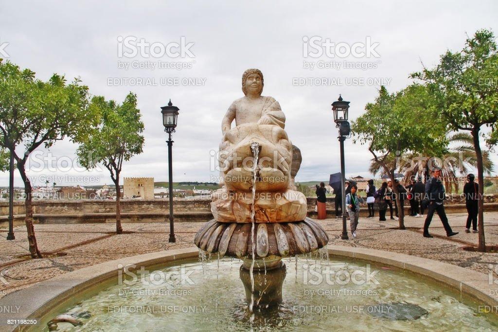 Cordoba, Andalusia, Spain - March 13, 2017 - Garden with fountain and San Rafaels Gate Bridge Triumph Monument (Triunfo de San Rafael) at Puerta del Puente in Plaza del Triunfo (Square of Triumph of San Rafael) stock photo