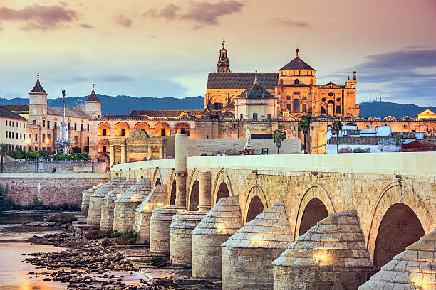 Cordoba, Spain at the Roman Bridge and Mosque-Cathedral Cordoba, Spain view of the Roman Bridge and Mosque-Cathedral on the Guadalquivir River. cordoba spain stock pictures, royalty-free photos & images