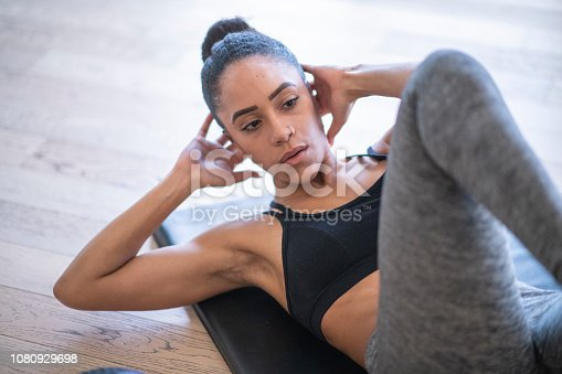 A woman wearing athletic clothing is in a gym. She is doing an ab workout.