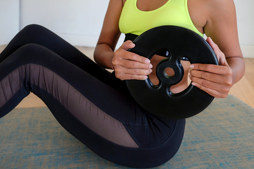 Close up shot of fit woman doing core exercise ( Russian twist ) with weight plates, during Covid 19 lockdown at home